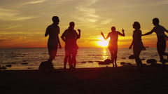 Group of Happy Young People are Dancing on the Beach in Sunset Light - stock footage