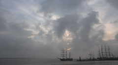 Tall ships leaving harbor with evening clouds Stock Footage