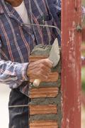 Bricklayer working in construction site of  brick wall - stock photo