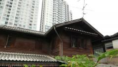 Huge condo tower building after small wooden house, panning shot Stock Footage