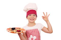 Happy little girl cook with crepes and ok hand sign Stock Photos