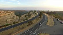 Taking off over a highway in a ridge, 4K aerial Stock Footage