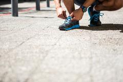 Athletic man tying his shoe laces - stock photo