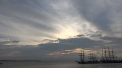 Tall ships leaving harbor timelapse cloudy sunset time Stock Footage