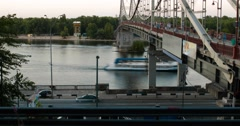 Evening motion of crowd, river and cars near a bridge across Dnieper river Stock Footage