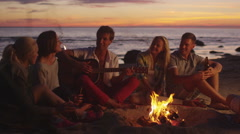 Group of Friends Sitting near Campfire at Night and Hanging Out Stock Footage