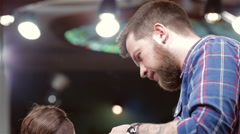 beard barber making haircut to hipster client - stock footage