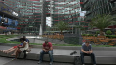 People playing with their phones and talking at the Sony Center, Berlin Stock Footage
