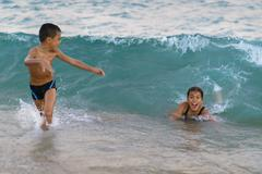 Happy kids playing at sea. Big wave coming on them Stock Photos