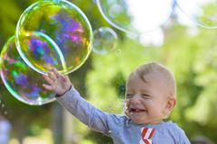 Cute baby catching soap bubbles in a summer day Stock Photos