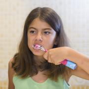 Beautiful girl brushing teeth looking in the mirror - stock photo