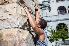 Stock Photo of Extreme athlete gripping to wall