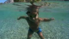 Toddler gets into the sea and swims underwater Stock Footage