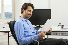 Young man reading written agreements for work - stock photo