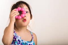 Child Looking Though Donut / Little Girl Looking Though Donut Background - stock photo