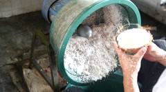Cocunut grating.mp4Man grating old coconut flesh with traditional grater machine - stock footage