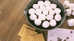 Preparing smores dip prepared with large marshmallows in cast iron pan. Stock Footage