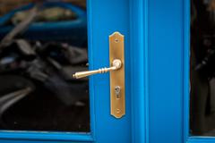 Brass door handle on a colorful blue door Stock Photos
