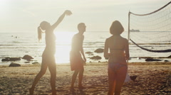 Stock Video Footage of Group of Young People Playing in Beach Volleyball in Sunset Light. Slow motion.