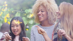 4K Joyful mixed ethnicity female friends holding sparklers at outdoor party - stock footage