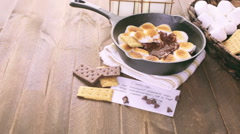Smores dip prepared with large marshmallows in cast iron pan. Stock Footage