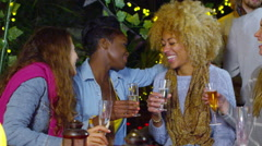 Happy mixed ethnicity female friends chatting over drinks at outdoor party Stock Footage