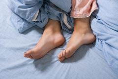 Bare Feet of a Young Woman on Blue Bed Stock Photos