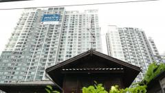 Small old house roof against modern skyscraper apartments building Stock Footage