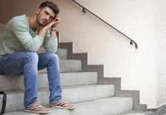 Casual  young man sitting on steps - stock photo