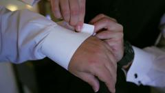 Groom cufflinks put on by best man Stock Footage