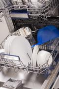 Dishwasher loades in a kitchen with clean dishes - stock photo