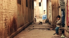 Indian boy and other people on a street in Varanasi, India Stock Footage