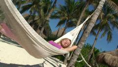 Young girl happy swinging in tropical park on hammock Stock Footage