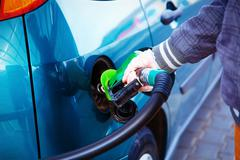 man pumping gasoline fuel in car at gas station. transportation concept - stock photo