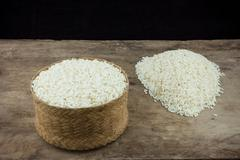 Rice in a wicker rice and scattered near on dark wooden table - stock photo
