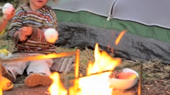 The boy and the girl fry a zephyr on a fire Stock Footage