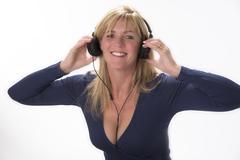 Woman using headphones to listen to music Stock Photos