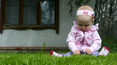 Seven months year old baby girl plays on a lawn Stock Footage