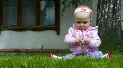 Seven months year old baby girl plays on a lawn with a flower Stock Footage