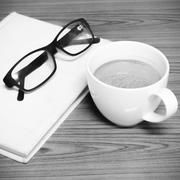 coffee cup and notebook with glasses black and white color tone style - stock photo