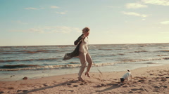 Happy woman playing on the beach with dog Stock Footage