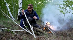 Male hiker lights and blazing fire in the forest in order to prepare food Stock Footage