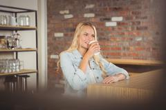 Stock Photo of Smiling blonde drinking out of take-away cup