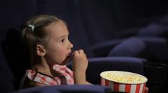 Beautiful little girl waching movie in the cinema - stock footage
