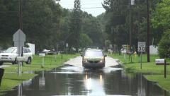 SUV Drives Down Street With Large Puddle Of Floodwater Stock Footage