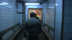 Two Men go Through an Underground Corridor Stock Footage