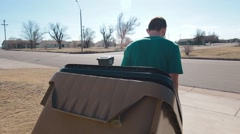 Man Taking Trash Can To Street Stock Footage