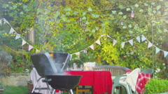 4K Outdoor summer party scene with flaming bbq, party banners and string lights. - stock footage