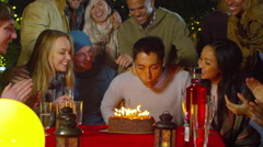 Happy group of friends at birthday party, man blows out candles on his cake Stock Footage