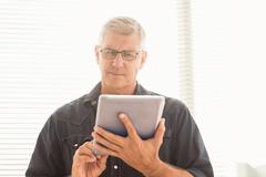 Attentive businessman scrolling on his tablet Stock Photos